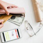 mãos de mulher segurando carteira com dólar turismo nela